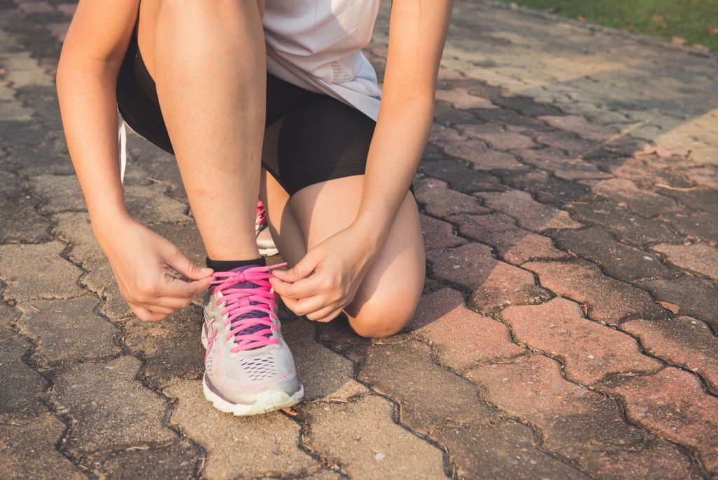 woman lacing up her running shoe