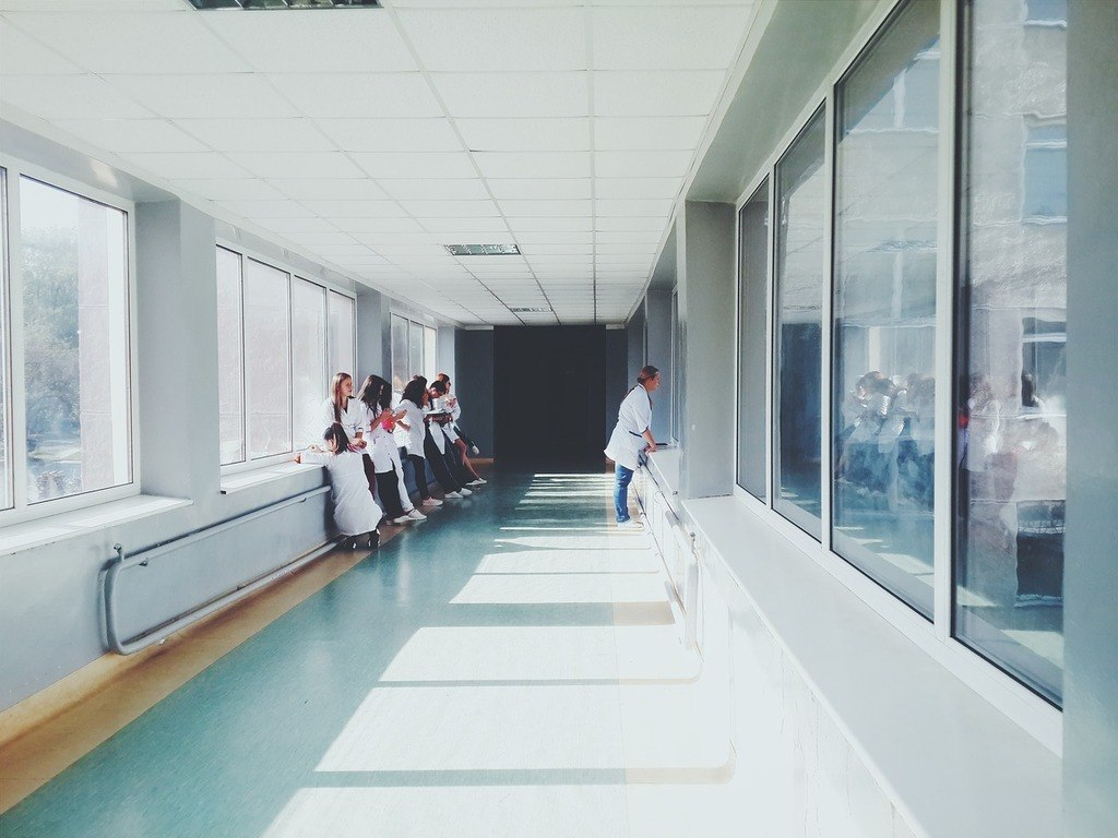 A group of nurses in Clove shoes stand together in the hallway of a hospital.